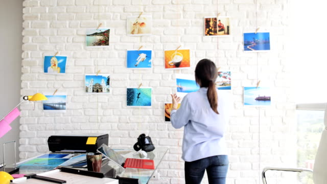 spansktalande kvinna som arbetar som fotograf kontrollera bilder i studio - hänga bildbanksvideor och videomaterial från bakom kulisserna