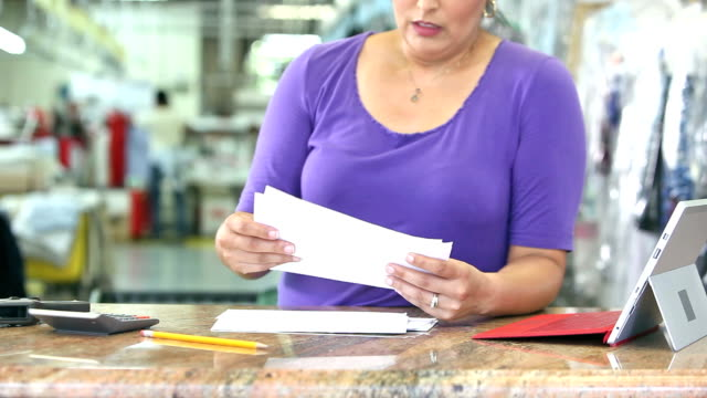 Hispanic woman working at dry cleaners paying bills video