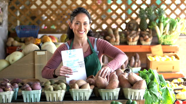 hispanic woman working at produce stand - retail worker stock videos and b-roll footage