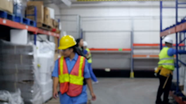 Hispanic woman working in warehouse walks into focus and smiles at camera video