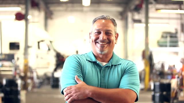 Hispanic worker in trucking industry, smiling at camera video