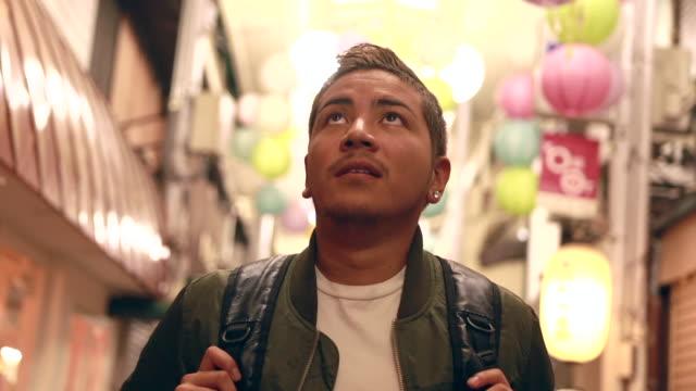 hispanic young man visiting old market in kyoto - tradycja filmów i materiałów b-roll
