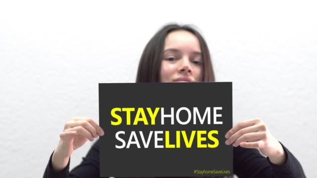 vídeos y material grabado en eventos de stock de mujer joven hispana sosteniendo un letrero para quedarse en casa salva vidas. pandemia 2019 coronavirus 2019-ncov. - stay home