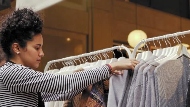 vídeos de stock e filmes b-roll de hispanic young woman looking and choosing for garment is a store - etnicidade ibérica