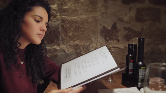 Hispanic young woman reading menu and ordering ready to dining in a restaurant Hispanic young woman reading menu and ordering ready to dining in a restaurant. Madrid, Spain. menu stock videos & royalty-free footage