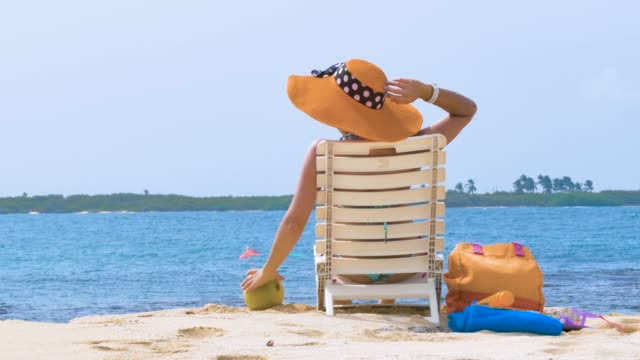 Hispanic Young woman refreshing with a coconut drink in a tropical white sand island beach in the Caribbean sea video