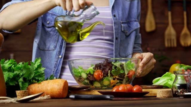 insalata di condimento della giovane donna ispanica in cucina rustica - olio d'oliva video stock e b–roll