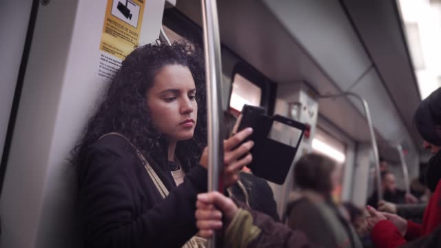 Hispanic young woman text messaging and using mobile phone while traveling in the train or subway Hispanic young woman text messaging and using mobile phone while traveling in the train or subway. Madrid, Spain underground stock videos & royalty-free footage