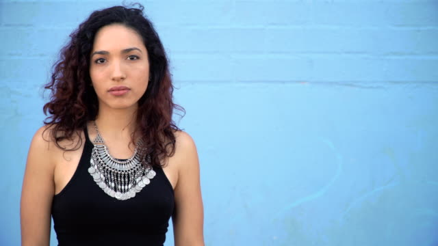 Hispanic Young woman with Sensual Attitude Serious and sensual curly haired Hispanic young woman posing against building wall. face to face stock videos & royalty-free footage