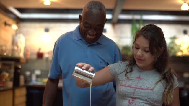 vídeos de stock, filmes e b-roll de hispano-latino avô ensinar o neto a cozinhar em casa - eles estão preparando o brigadeiro brasileiro - brigadeiro