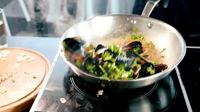 Hissing mussels in frying pan. Chef mixing seafood with oil and seasonings