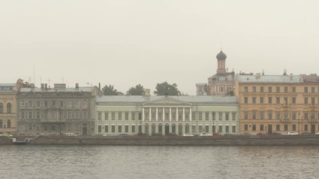 Historic homes on an embankment of the Neva river in cloudy morning - St. Petersburg, Russia video
