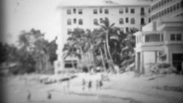 1953: Historic Moana Surfrider beach hotel with tourists frollicking about. video