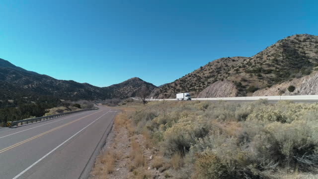 Historic Route 66 and modern Highway 40 near Tijeras, between mountains covered by Cibola National Forest, not far from Albuquerque, New Mexico. Aerial drone video with the backward camera motion