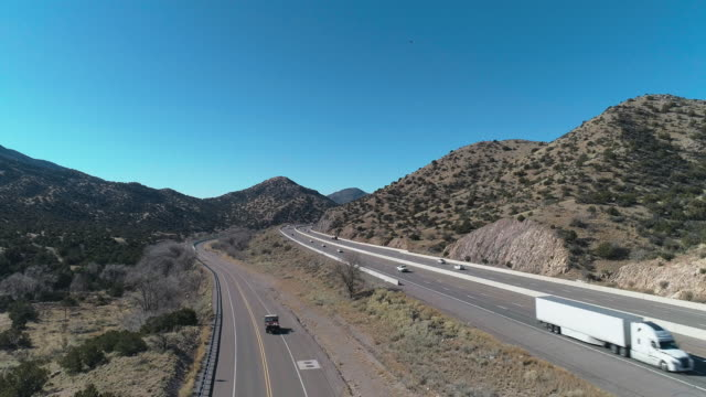 Historic Route 66 and modern Highway 40 near Tijeras, between mountains covered by Cibola National Forest, not far from Albuquerque, New Mexico. Aerial drone video with the descending camera motion