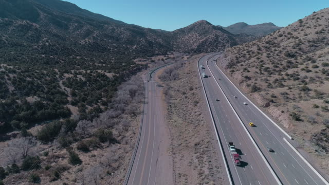 Historic Route 66 and modern Highway 40 near Tijeras, between mountains covered by Cibola National Forest, not far from Albuquerque, New Mexico. Aerial drone video with the forward and ascending camera motion