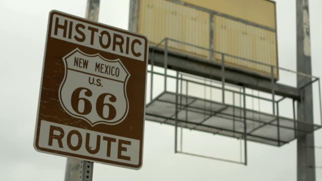 stockvideo's en b-roll-footage met 4k historische route 66 verkeersbord santa rosa, new mexico met vervallen billboard - arizona highway signs