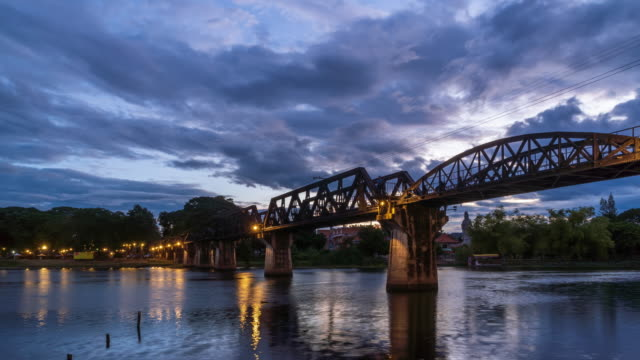 Historical bridge over River Kwai, and Death Railway, built by Japanese and prisoner during World War II, Kanchanaburi, Thailand; day to night - Time Lapse