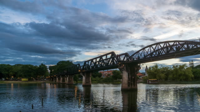 Historical bridge over River Kwai, and Death Railway, built by Japanese and prisoner during World War II, Kanchanaburi, Thailand; day to night, zoom in - Time Lapse