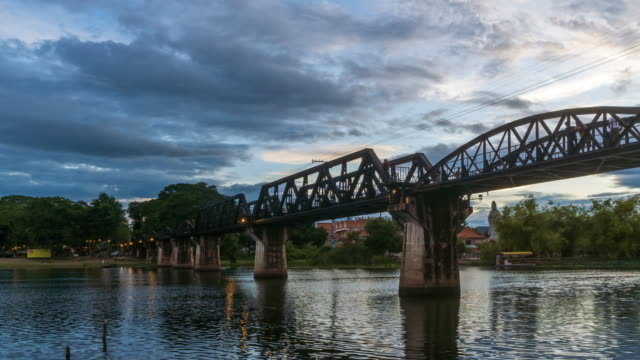 Historical bridge over River Kwai, and Death Railway, built by Japanese and prisoner during World War II, Kanchanaburi, Thailand; day to night, zoom out - Time Lapse