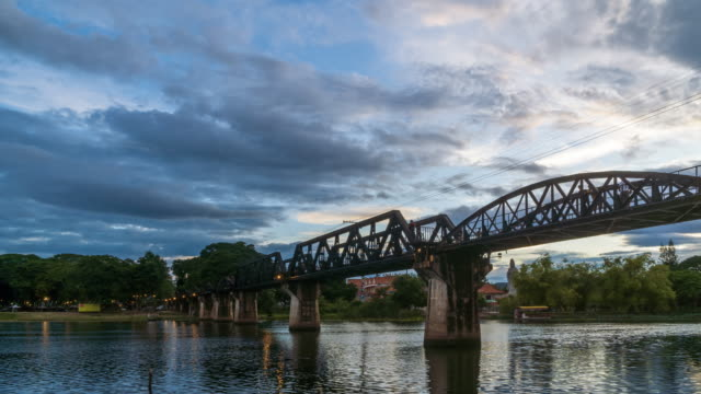 Historical bridge over River Kwai, and Death Railway, built by Japanese and prisoner during World War II, Kanchanaburi, Thailand; day to night, tilt down - Time Lapse