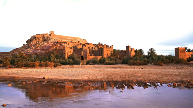 Historical complex of Aït Benhaddou. Old brick village on the desert Ait Benhaddou surrounded by palm trees and desert desert oasis stock videos & royalty-free footage