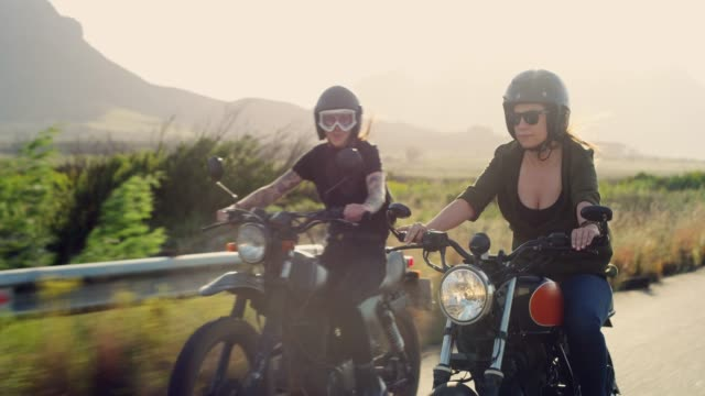 Hitting the road on our bikes 4k video footage of two young women riding their motorcycles on the open road crash helmet stock videos & royalty-free footage