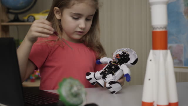 Hobby Future. Genius Schoolgirl  Assembling Robots in Modern Classroom. Little Girl Assemble Robot at Home. Education Science, Technology Children, Programming Electronic Robotics School Lesson.
