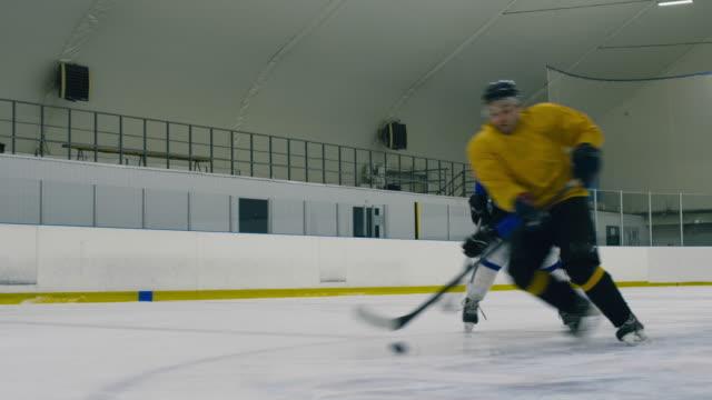 vídeos de stock e filmes b-roll de hockey player following another from opposite team - liga desportiva