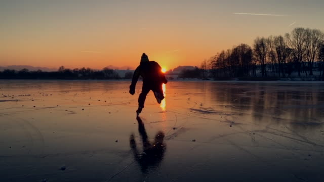 Hockey player skating on a frozen lake into sunset