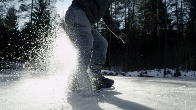 zwolnione tempo zbliżenie: hockey player zatrzymuje się przed kamerą - łyżwa filmów i materiałów b-roll