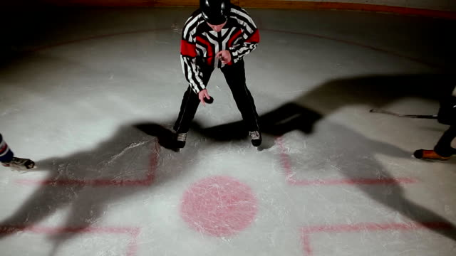 hockey referee produces a faceoff and the two players begin to fight for the puck - hockey stock videos and b-roll footage