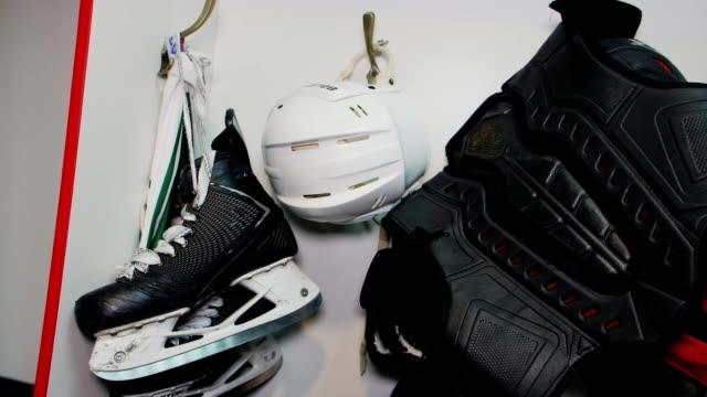 stockvideo's en b-roll-footage met hockey schaatsen helm en beschermende vest hangen in teamkamer - sportcompetitie