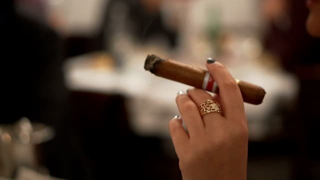 Holding a cigar in a bar Woman holding a cigar in a bar narcotic stock videos & royalty-free footage