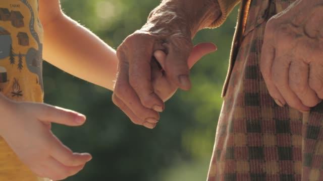 holding hands. detail of a child's hands holding the senior woman hands - babka dziadek i babcia filmów i materiałów b-roll
