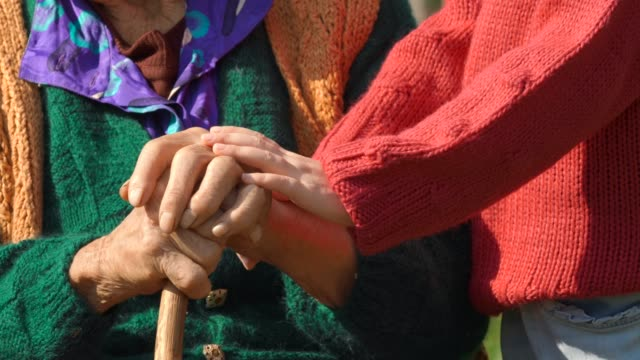 Holding Hands. Detail of a Child's Hands Holding the Senior Woman Hands video