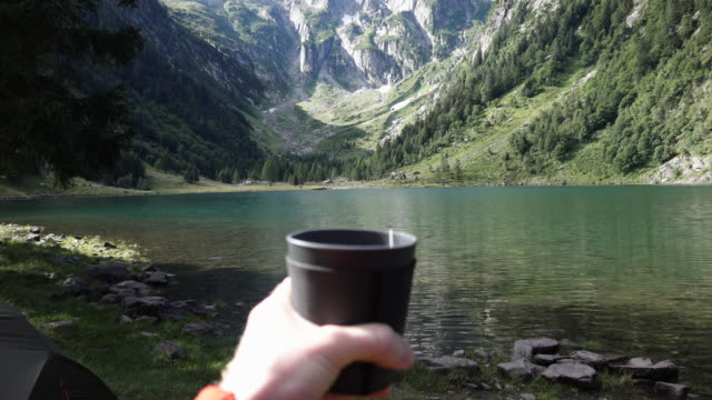 POV holding hope beverage looking out at view of lake and mountains Exploring nature in Ticino rack focus stock videos & royalty-free footage