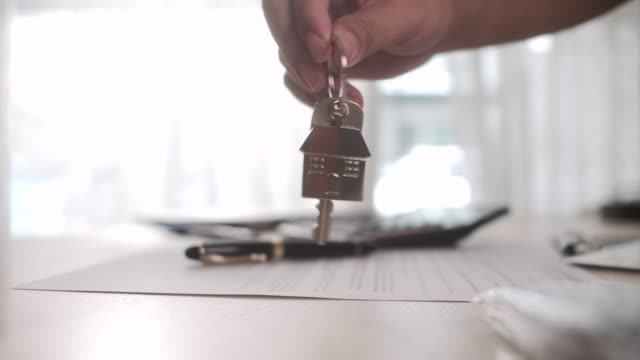 holding keys of a new home on a house shaped key ring