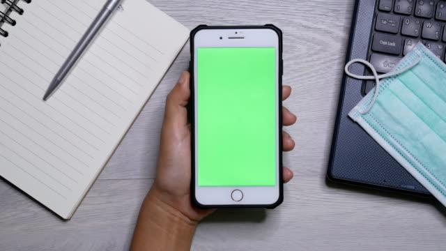 halten smartphone chroma schlüssel hochwinkel-ansicht - smartphone mit corona app stock-videos und b-roll-filmmaterial