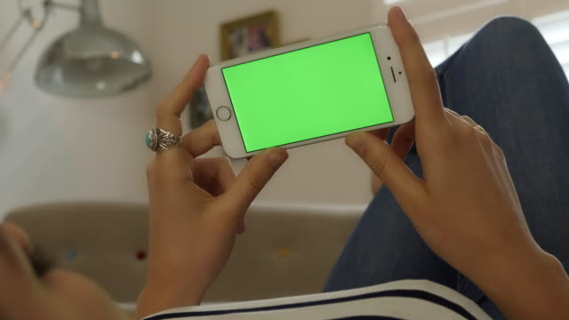 vídeos de stock e filmes b-roll de holding smartphone with chromakey screen. woman lying down indoors looking at her phone. - segurar