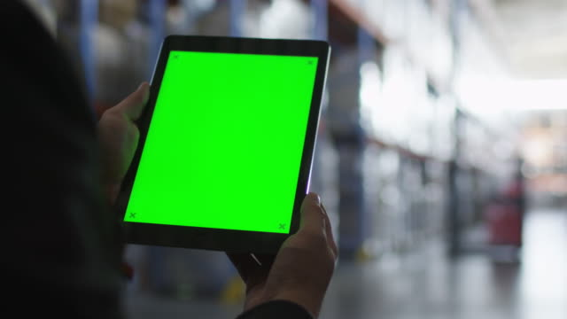 Holding Tablet PC with Green Screen in Logistic Warehouse. Mock-up. - vídeo