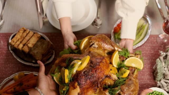 tavolo delle vacanze. le mani femminili mettono pollo fritto sul tavolo. piatti di natale. - christmas table video stock e b–roll