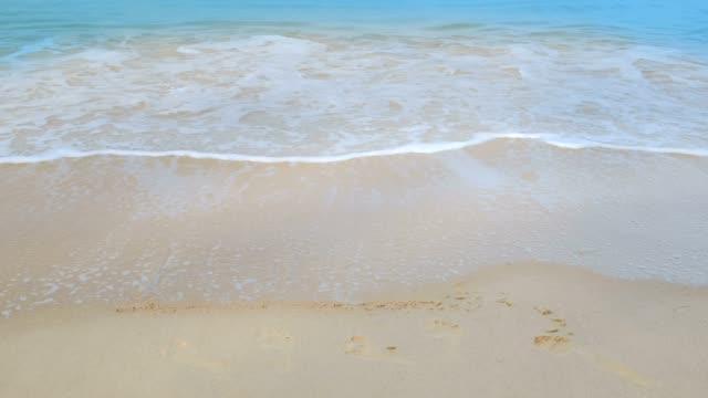 vidéos et rushes de texte de vacances sur le sable et les vagues douces s'écrasant sur la plage de phuket avec des vagues mousseuses venant au rivage, l'eau bleue de mer - mer d'andaman