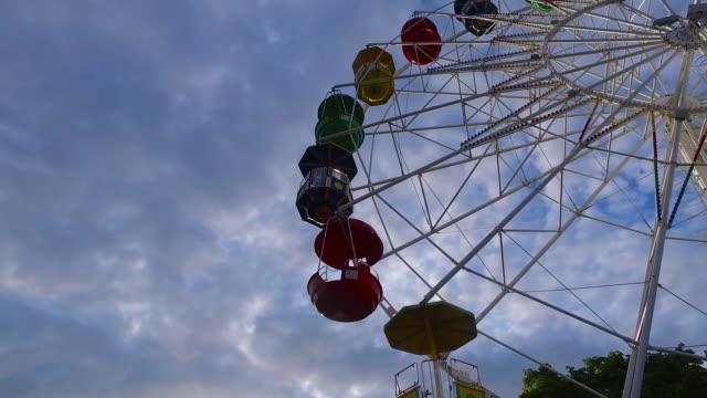 Holidays in amusement park. Revolves wheel on the attraction 'Ferris wheel'. Beautiful summer evening. video