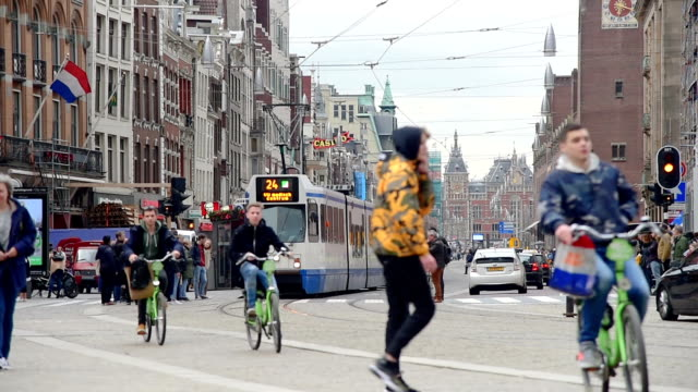 Holland Netherlands view. Street and Amsterdam canal, bicycles and cyclists, houseboats, living boats. View on Amsterdam from  street with row of shops; tram, tourists and bicycle iin Amsterdam. Amsterdam is capital of the Netherlands. dutch architecture stock videos & royalty-free footage