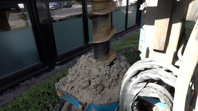 stockvideo's en b-roll-footage met holle boorgatvijzel van een droog boorplatform boort een gat in de zandgrond en produceert zand aan de zijkanten. - geologie