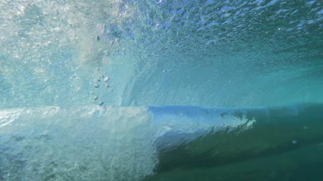 yavaş hareket sualtı: dalga içi boş boru şekillendirme ve açık okyanusa haddeleme - yuvarlanmak stok videoları ve detay görüntü çekimi