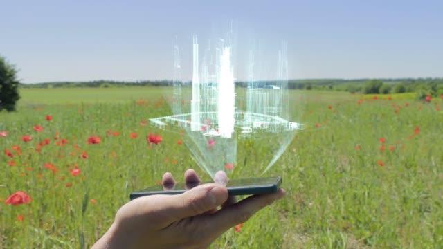 hologramm der modernen stadt auf einem smartphone - smart city stock-videos und b-roll-filmmaterial