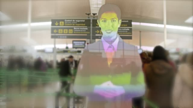 Holographic Annunciator At Barcelona Airport The technology uses an optical illusion to create a hologram of a real person which provides helpful information for passengers at the security gates.  The virtual assistant can be found at the security filters of terminals T1 and T2B, informing passengers of the necessary steps to access and pass through the security checkpoint ahead. Detailed information, given by the assistant, ensures passengers arrive at the checkpoint with all their belongings ready for inspection. Security messages are provided in five different languages including Catalán, Castilian Spanish, English, Russian and Chinese. hologram stock videos & royalty-free footage