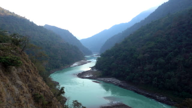 Holy Ganges river flowing among the green mountains of Rishikesh, India.